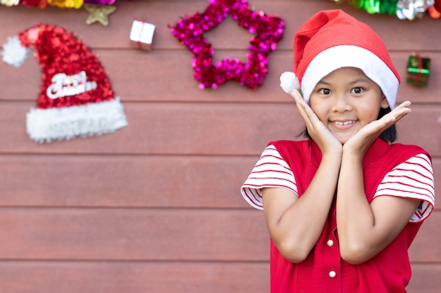 Young girl in red dress shows heart shape from hands after received greetings in christmas
