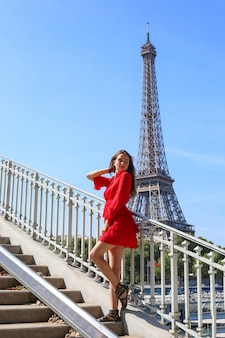 Young girl in red dress stands alone on bridge in paris on the eiffel tower background