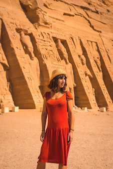 A young girl in red dress visiting the egyptian temple of nefertari near abu simbel in southern egypt in nubia next to lake nasser. temple of pharaoh ramses ii, travel lifestyle
