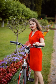 Young girl in red dress with retro bycicle in the park