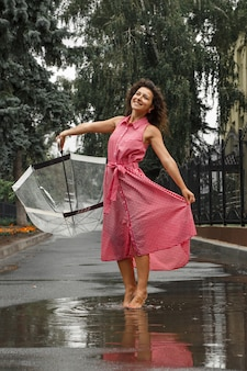 Young girl in a red dress with a transparent umbrella dancing in the rain standing in a puddle