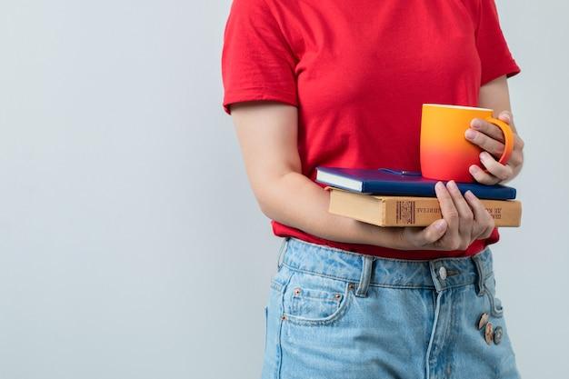 Giovane ragazza in camicia rossa che tiene libri e una tazza di bevanda
