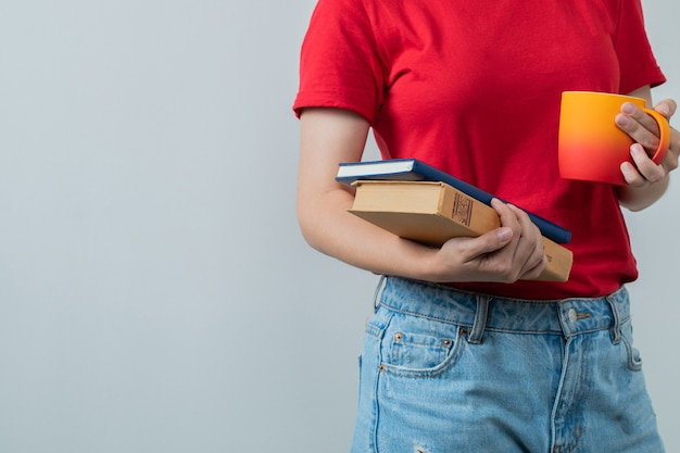 Ragazza in camicia rossa che tiene una tazza di bevanda