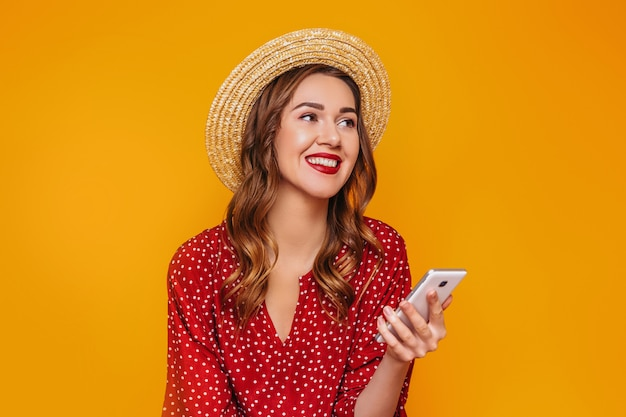 Young girl in a red summer dress a straw hat with red lips holds a mobile phone a smartphone in her hands laughs smiles and looks at  isolated on a yellow orange wall