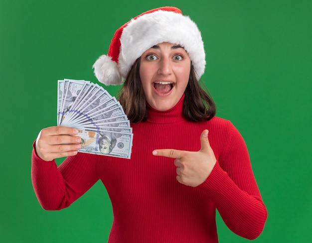 Young girl in red sweater and santa hat holding cash pointing with index finger at money happy and surprised standing over green wall