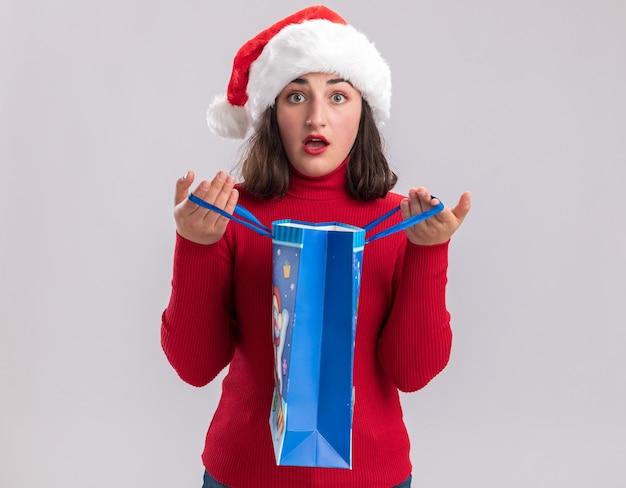 Giovane ragazza in maglione rosso e cappello da babbo natale che tiene in mano un sacchetto di carta colorato con regali di natale che guarda l'obbiettivo sorpreso in piedi su sfondo bianco