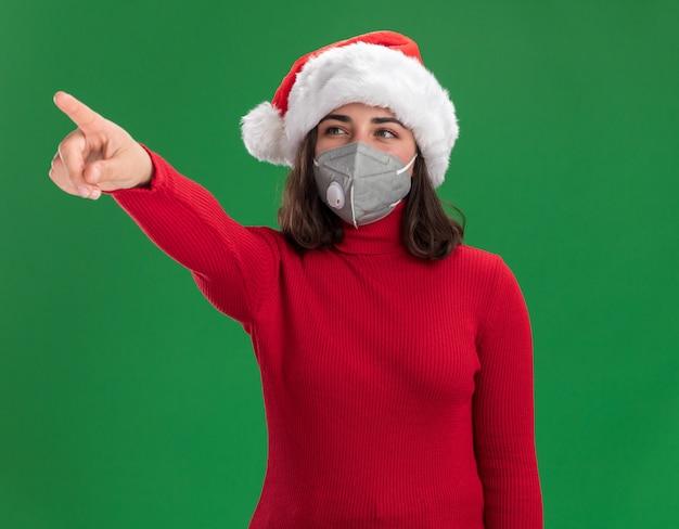 Giovane ragazza in maglione rosso e cappello da babbo natale che indossa la maschera protettiva per il viso che guarda da parte con la faccia felice che punta con il dito indice a qualcosa in piedi sopra la parete verde