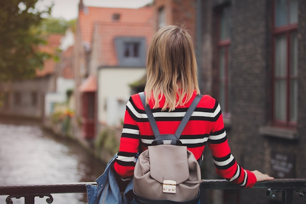 Young girl in red sweater at streets of bruges