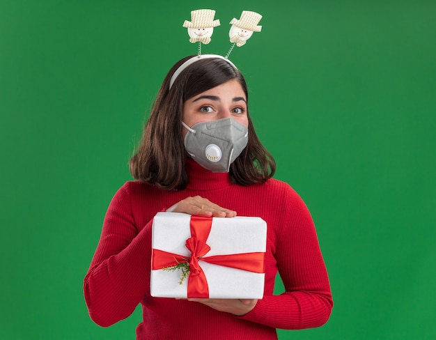 Giovane ragazza in maglione rosso con archetto divertente che indossa la maschera protettiva per il viso tenendo un presente con la faccia felice in piedi sopra la parete verde