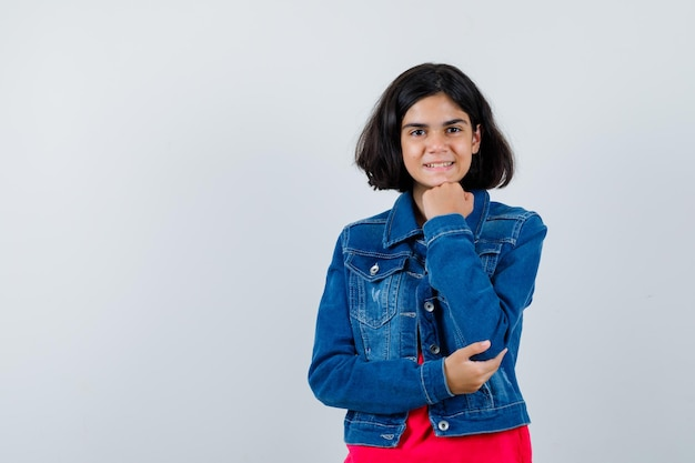 Giovane ragazza in maglietta rossa e giacca di jeans che si appoggia il mento sulla mano, sorride e sembra felice