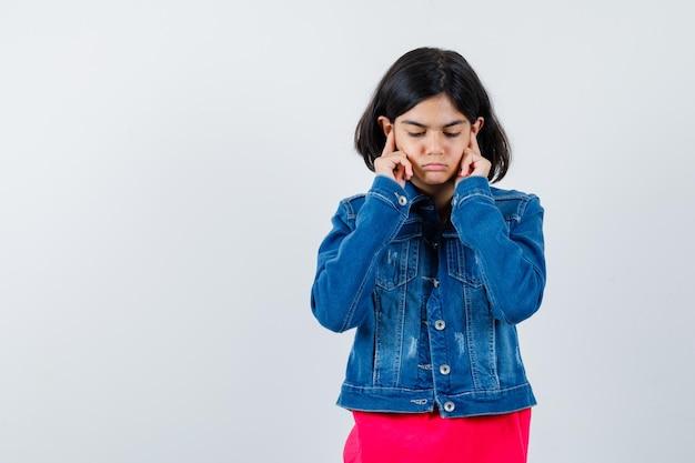 Giovane ragazza in maglietta rossa e giacca di jeans che tappa le orecchie e sembra carina, vista frontale.