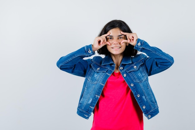 Young girl in red t-shirt and jean jacket pointing eyes and looking happy