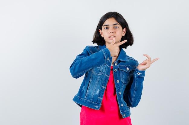 Giovane ragazza in maglietta rossa e giacca di jeans che punta a destra con l'indice e sembra carina, vista frontale.