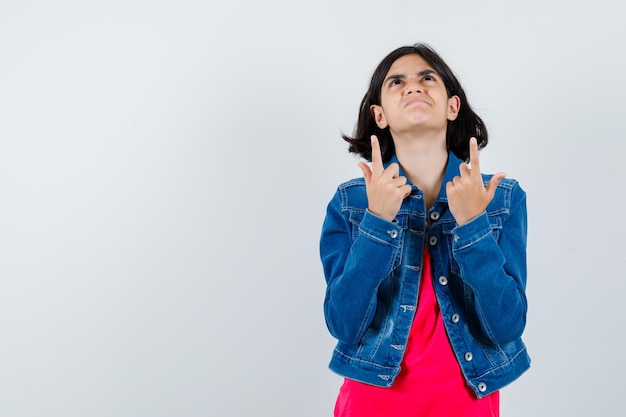 Giovane ragazza in maglietta rossa e giacca di jeans che punta verso l'alto e sembra carina, vista frontale.