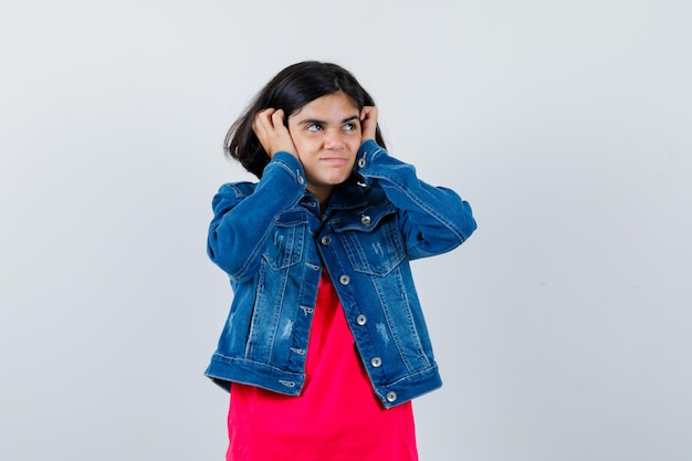 Young girl in red t-shirt and jean jacket pressing hands on ears and looking happy , front view.