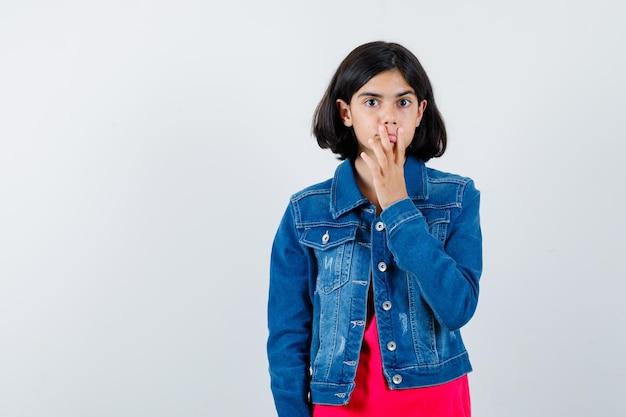 Giovane ragazza in maglietta rossa e giacca di jeans che mette la mano sulla bocca e sembra carina, vista frontale.