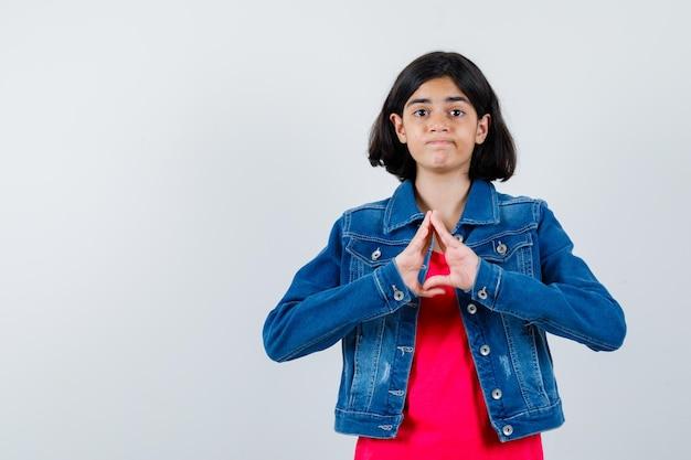 Giovane ragazza in maglietta rossa e giacca di jeans che mostra gesto di assicurazione e sembra carina, vista frontale.
