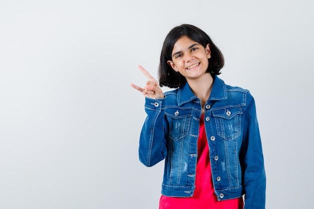 Giovane ragazza in maglietta rossa e giacca di jeans che mostra il gesto del rock n roll e sembra carina, vista frontale.