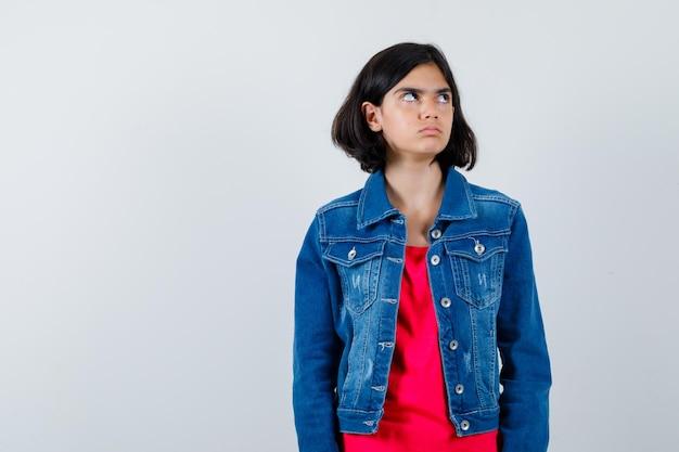 Giovane ragazza in maglietta rossa e giacca di jeans in piedi dritta, guardando lontano e posando alla telecamera e guardando carina, vista frontale.