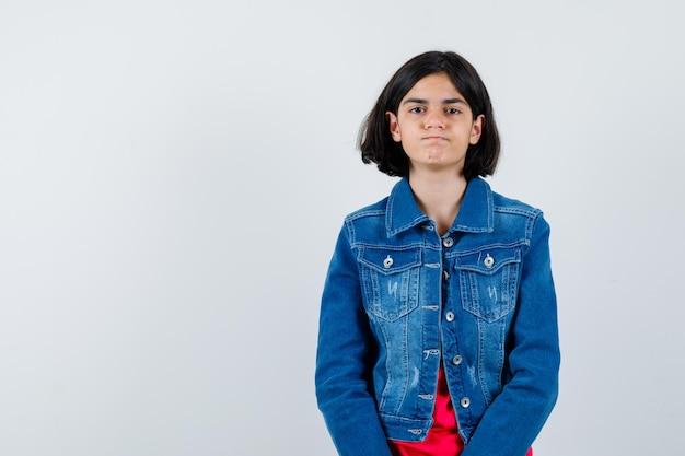 Giovane ragazza in maglietta rossa e giacca di jeans in piedi dritta e in posa davanti alla telecamera e sembra carina