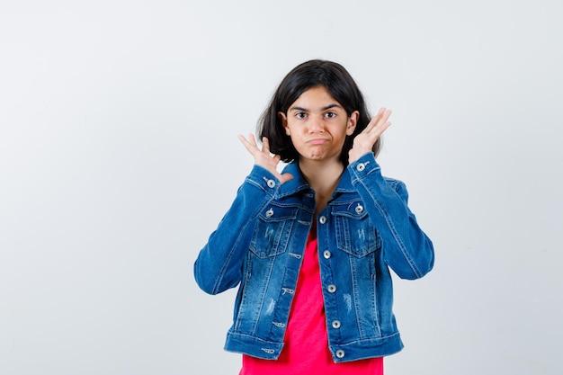 Giovane ragazza in maglietta rossa e giacca di jeans che allunga le mani mentre tiene qualcosa di immaginario e sembra carina, vista frontale.