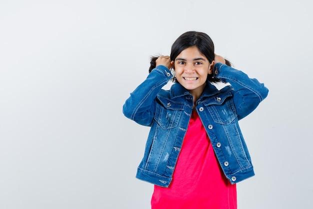Giovane ragazza in maglietta rossa e giacca di jeans che rimbocca i capelli con le mani e sembra carina, vista frontale.
