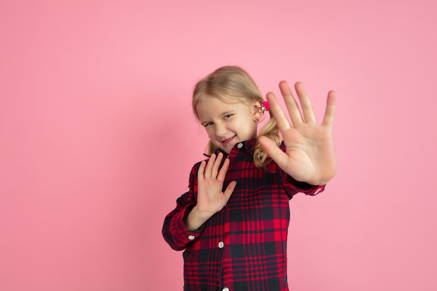 Young girl rejecting on pink wall