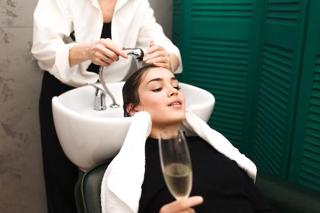 若い女の子が髪を洗いながらシャンパングラスでビューティーサロンでリラックス