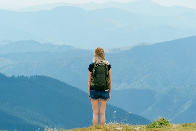 편안 하 고 산 꼭대기 경치를 즐기고 어린 소녀. 행복, 행복 아름다운 여름 자연 풍경입니다. 외로운 젊은 금발 십 대 여행자 휴가 야외 꿈. 낭만적 인 분위기