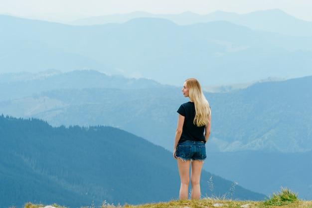 편안 하 고 산 꼭대기 경치를 즐기고 어린 소녀.