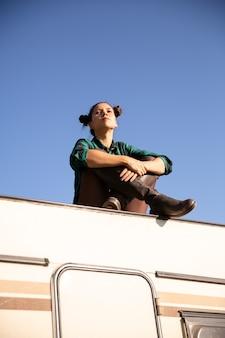 복고풍 캠핑카의 지붕에서 편안한 어린 소녀. 휴식 시간