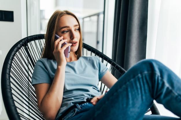アームチェアで休んで、自宅の窓の近くで電話で話している若い女の子