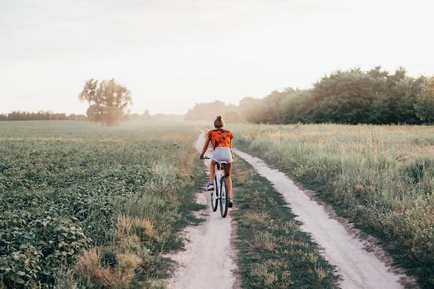 Молодая девушка едет на велосипеде по дороге