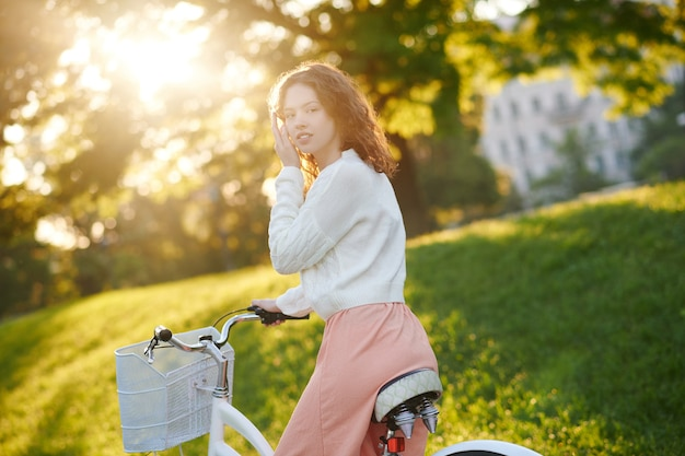 A young girl riding a bike in sunlight in the park