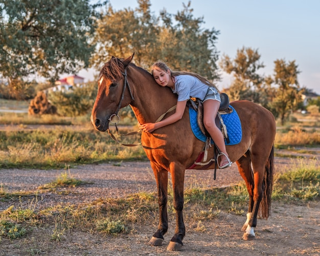 A young girl riding a horse in the evening light of the sunset natural light Premium Photo