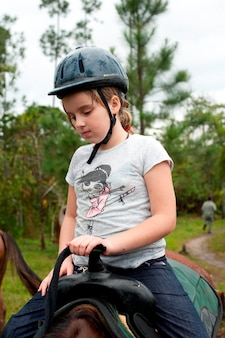 Young girl riding a horse at mountain pine ridge reserve in belize