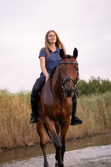 A young girl riding a horse on a shallow lake, a horse runs on water at sunse