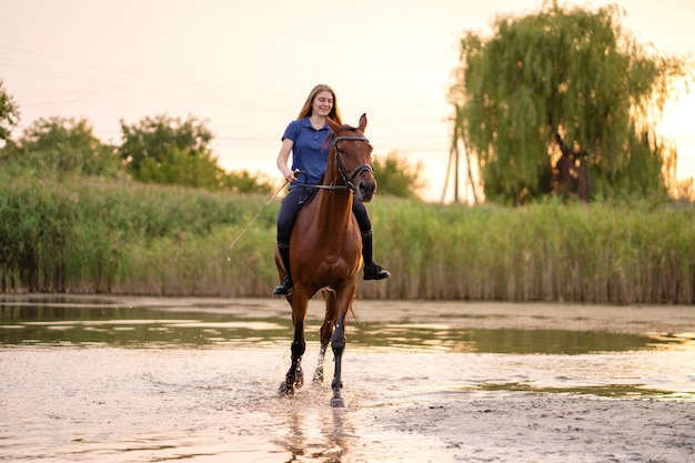 A young girl riding a horse on a shallow lake at sunset.