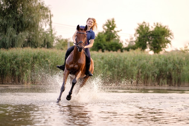 Young girl riding a horse on a shallow lake