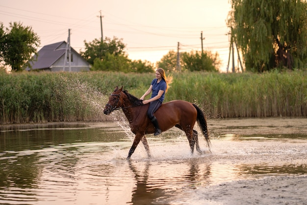 A young girl riding a horse on a shallow lake.
