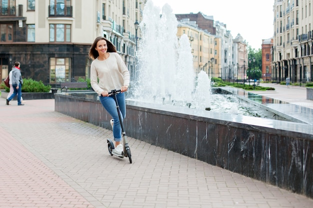 A young girl riding a scooter.