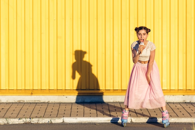 어린 소녀 rollerskating 및 노란색 벽에 아이스크림을 먹고