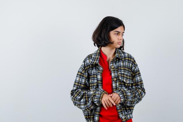 어린 소녀가 손을 문지르고 체크 셔츠와 빨간 티셔츠를 입고 진지한 표정을 짓고 있습니다. 전면보기.