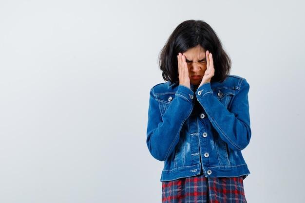 체크 셔츠와 진 재킷을 입고 관자놀이를 문지르고 짜증을 내는 어린 소녀. 전면보기.