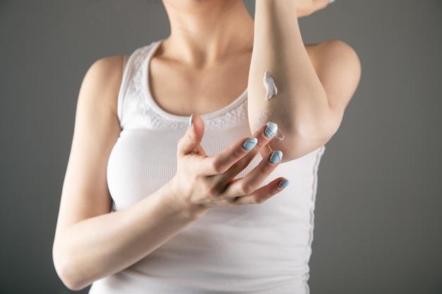 Молодая девушка трет руки кремом о серую стену