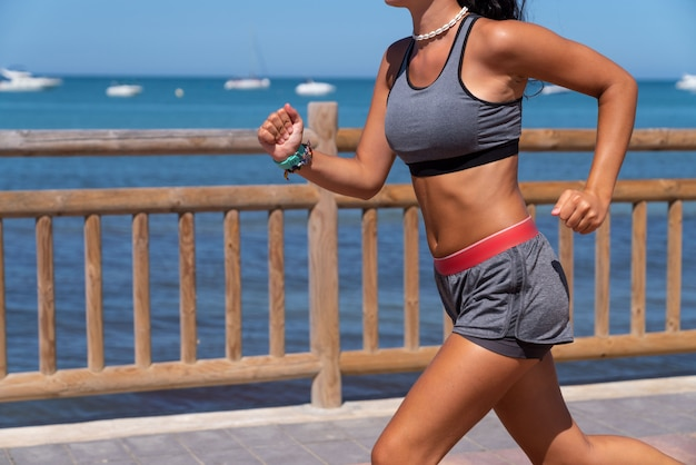 Young girl running on the beach with top and smartwatch and shorts and top on