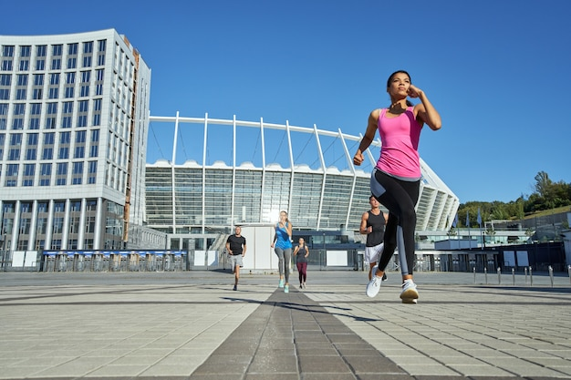 Young girl running in front of other sportsmen