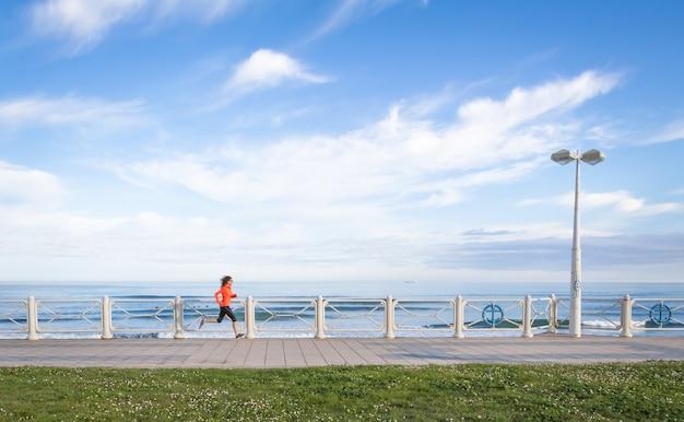 여름에 해변 산책로에서 달리는 어린 소녀