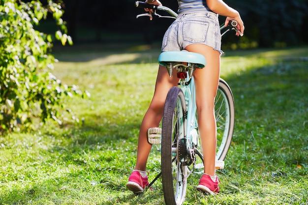 공원에서 푸른 잔디에 복고풍 자전거와 함께 서있는 분홍색 운동화를 입고 어린 소녀의 황갈색 다리 공간을 복사합니다.
