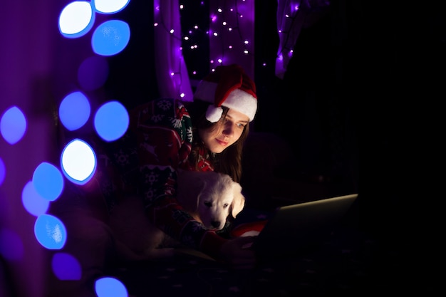Young girl in a santa claus hat with a laptop